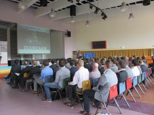 mensen in een zaal bij lezing over duurzaam bouwen